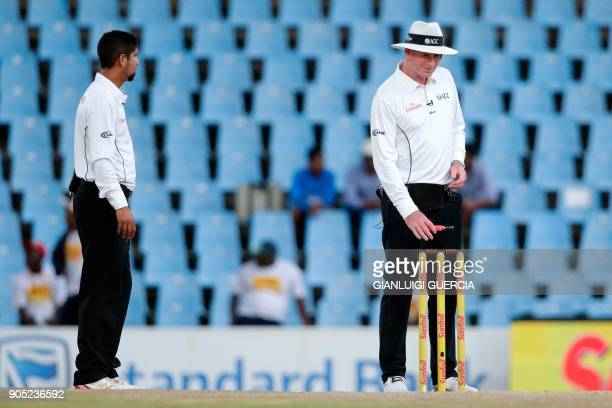 An umpire takes light measurement as play is suspended due to bad light during the third day of the second Test cricket match between South Africa...