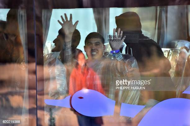 TOPSHOT An unaccompanied migrant minor from the demolished 'Jungle' migrant camp in Calais waves from a bus as he leaves for a reception centre on...