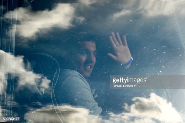 TOPSHOT An unaccompanied migrant minor from the demolished 'Jungle' migrant camp in Calais waves from a bus travelling to reception centres around...