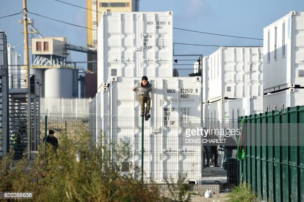 TOPSHOT An unaccompanied migrant minor living in specially outfitted shipping containers near the demolished 'Jungle' migrant camp in Calais climbs a...