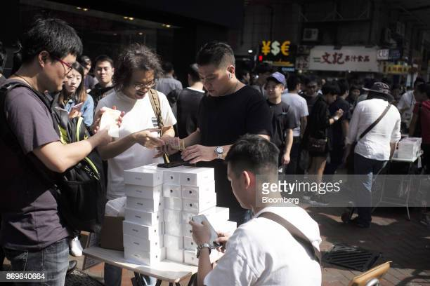 An unauthorized reseller center buying a newlypurchased Apple Inc iPhone X from a shopper second left hands over money to the shopper in the Mong Kok...