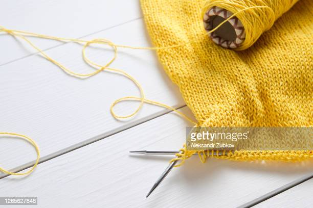 an unbound light summer sweater or cardigan made of cotton. next to it lies a skein of yarn and knitting needles, against the background of a white wooden table. freelance creative concept of work and life, hobbies. - knitting stock pictures, royalty-free photos & images