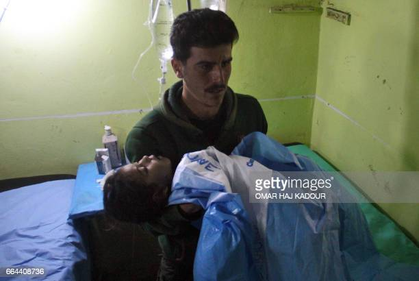 TOPSHOT An unconscious Syrian child is carried at a hospital in Khan Sheikhun a rebelheld town in the northwestern Syrian Idlib province following a...