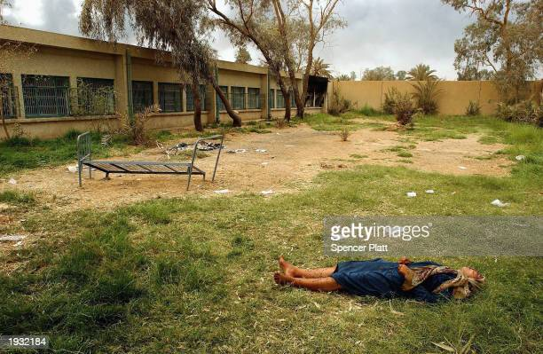 An unconscious woman lies in a courtyard April 15 2003 at a psychiatric hospital in Baghdad Iraq While most hospitals in Iraq are suffering the...