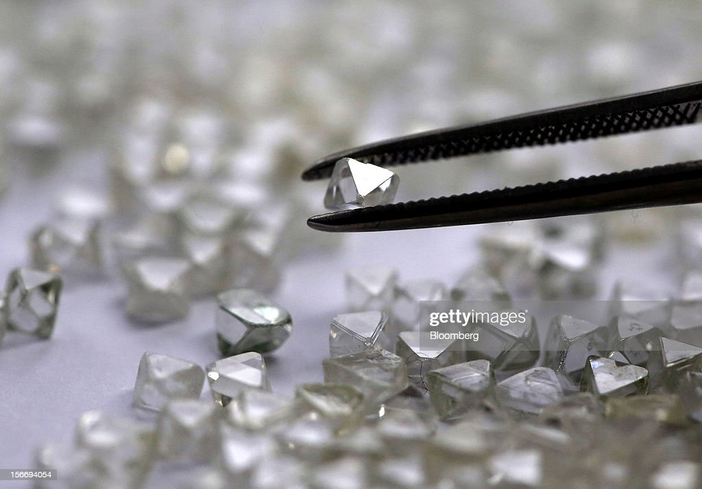 An uncut diamond is selected from a collection of colorless and colored diamonds from a sorting table at the De Beers office in London, U.K., on Friday, Nov. 16, 2012. De Beers, the biggest diamond producer by revenue, is moving the sorting and trading of rough stones to Botswana from London to secure access to the world's largest supplier of diamonds by value and challenge Antwerp's dominance as the world's biggest trading hub for rough diamonds. Photographer: Chris Ratcliffe/Bloomberg via Getty Images