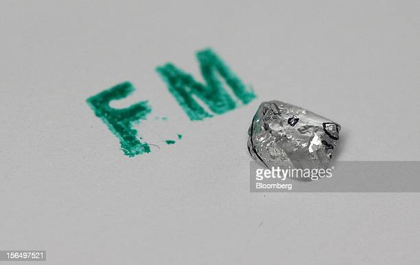 An uncut Forever Mark diamond is displayed with its cutting marks beside an identifying stamp at the Shrenuj Botswana Ltd sightholder office in...