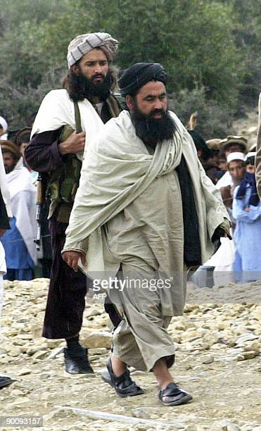 An undated photo from 2004 shows Pakistani Taliban chief Baitullah Mehsud escorted by his guard as he arrives for a meeting in South...