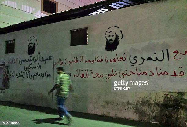 An undated picture taken in 2016 shows a man walking past images of executed Shiite cleric Nimr alNimr on a wall in the Awamiya area in Saudi...