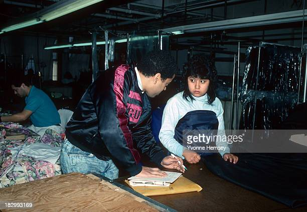 An underage immigrant worker at a sweatshop in Queens New York is photographed March 25 1990 when a Labor Department investigator makes a surprise...