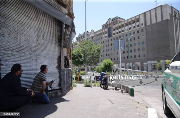 An undercover Iranian policeman holds a weapon outside the Iranian parliament in the capital Tehran on June 7 2017 during an attack on the complex...