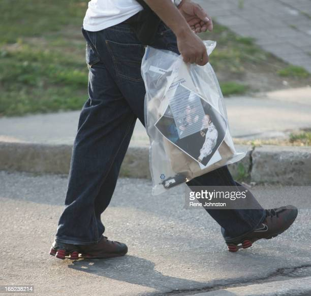 An undercover officer walks with bags of personal items from a raided home. A multi task force takedown of the Driftwood Crips in Jane and Finch area...