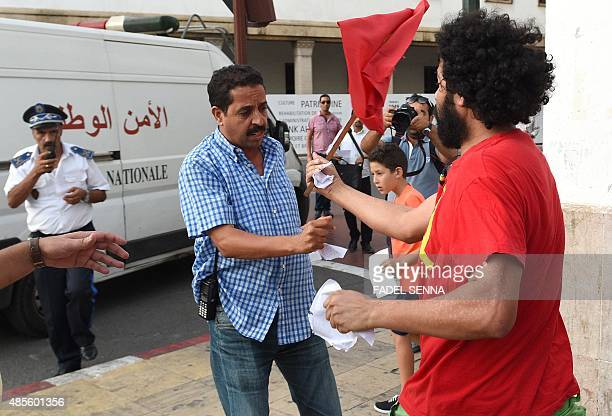 An undercover policeman tries to pull out leaflets from a supporter of the Moroccan party 'Ennahj dimocrati' distributing leaflets calling for the...