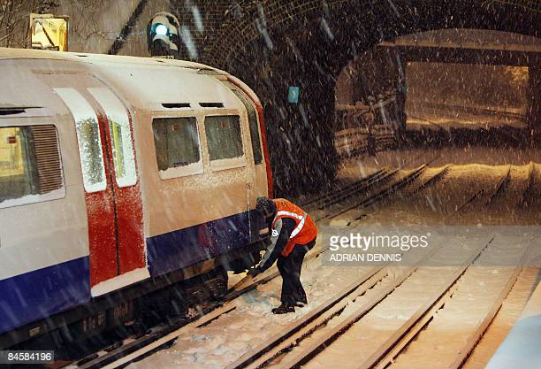 An underground worker attempts to release part of a tube train which had frozen and stalled at Osterley station in west London on February 2 2009 A...