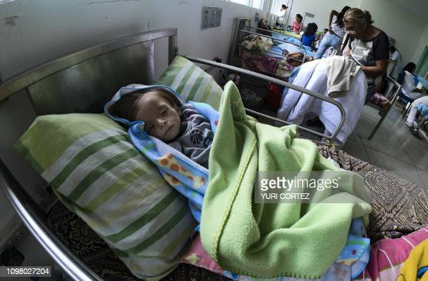 TOPSHOT An undernourished baby remains in a hospital bed in Maracay Aragua state Venezuela on February 7 2019 The drama of undernourished mothers and...