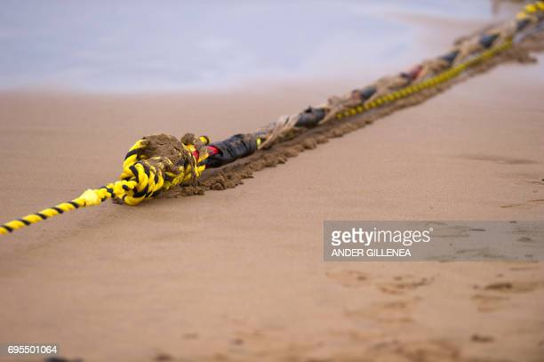 An undersea fiber optic cable is attached to a rope at Arrietara beach near the Spanish Basque village of Sopelana on June 13 2017 Facebook and...