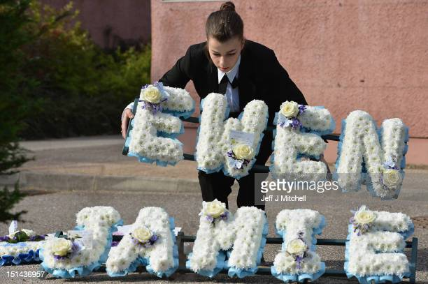 An undertaker carries flowers at the funeral of Ewan Beaton aged five and his brother Jamie aged two at Inverness Crematorium on September 9 201 in...