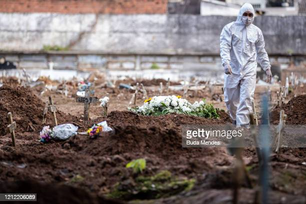 An undertaker walks among open graves amidst the coronavirus pandemic at the Caju cemetery on May 8, 2020 in Rio de Janeiro, Brazil. According to the...