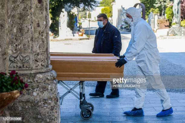 An undertaker wearing a face mask and overalls unloads a coffin out of a hearse on March 16, 2020 at the Monumental cemetery of Bergamo, Lombardy, as...