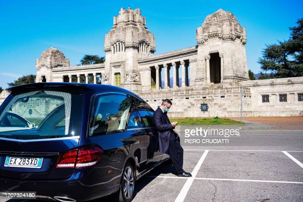 An undertaker wearing a face mask checks his smartphone as he waits by hearses on the parking lot of the Monumental cemetery of Bergamo Lombardy as...