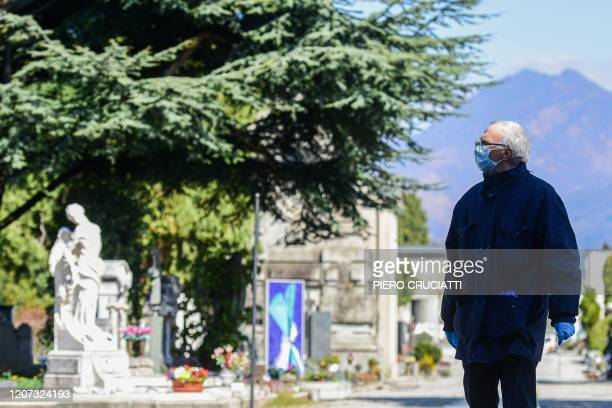 An undertaker wearing a face mask walks across the Monumental cemetery of Bergamo Lombardy as burials of people who died of the new coronavirus are...