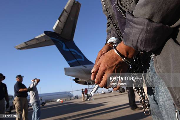 An undocumented Guatemalan immigrant chained for being charged as a criminal prepares to board a deportation flight to Guatemala City Guatemala at...