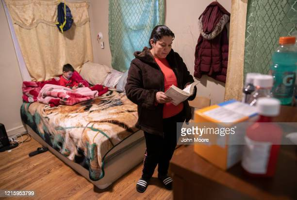 An undocumented Honduran immigrant reads her Bible during self-quarantine with her family for possible COVID-19 on March 30, 2020 in Mineola, New...