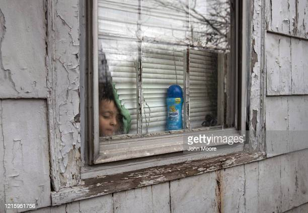 An undocumented Honduran immigrant sick and isolated with his family for the last two weeks, stands inside his bedroom window on March 30, 2020 in...