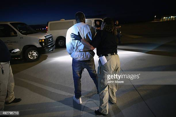 An undocumented immigrant is led towards an Immigration and Customs Enforcement charter jet early on October 15 2015 in Mesa Arizona The immigrants...