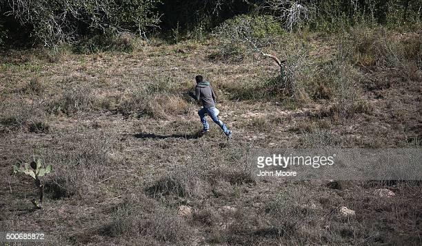 An undocumented immigrant runs from US Border Patrol agents on December 9 2015 near McAllen Texas Border security remains a key issue in the...