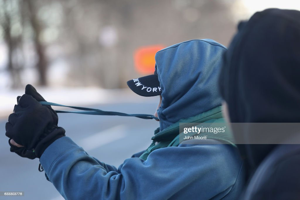 An undocumented immigrant tightens his hoodie against the cold while waiting for work in an official day laborer pick-up site on February 1, 2017 in Stamford, Connecticut. The city of Stamford has an official zone for employers to pick up day laborers, most of them undocumented immigrants, although many prefer to stand by nearby businesses for warmth. Stamford, CT is located in Fairfield County, considered a 'sanctuary county' for not reporting undocumented immigrants to federal authorities.