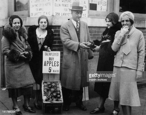 An unemployed man sells apples during the Great Depression location unknown USA circa 1930s Four women each with an apple stand around him and a sign...