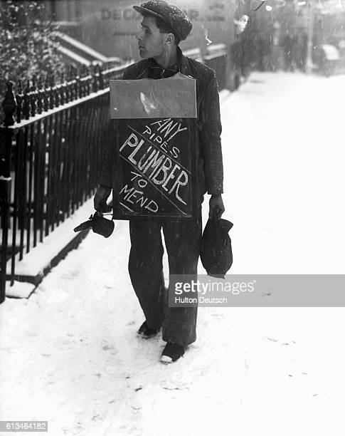 An unemployed plumber in 1938 wearing a sandwich board advertising his services
