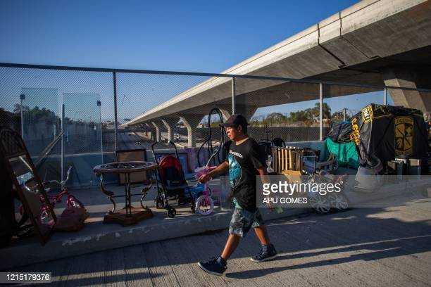 An unemployed upholsterer Israel Yaxon 28 yearsold who has lived for one year on the street walks outside his tent over the bridge of the 110 Freeway...