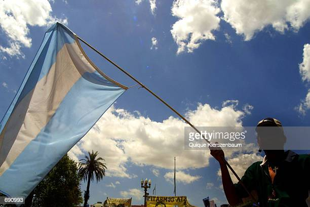 An unemployed worker waves a flag during a demonstration January 15 2002 at Plaza de Mayo in front of the government house Casa Rosada in Buenos...