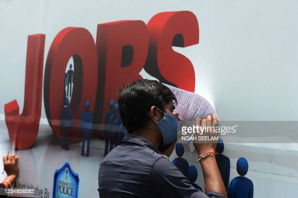 """An unemployed youth fills an application form to access job openings in the private sector outside an """"employment van"""" during an initiative by TMI..."""
