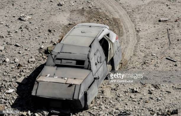 An unexploded car bomb is seen on the western frontline of Raqa after its driver was shot by members of the Syrian Democratic Forces on October 8...