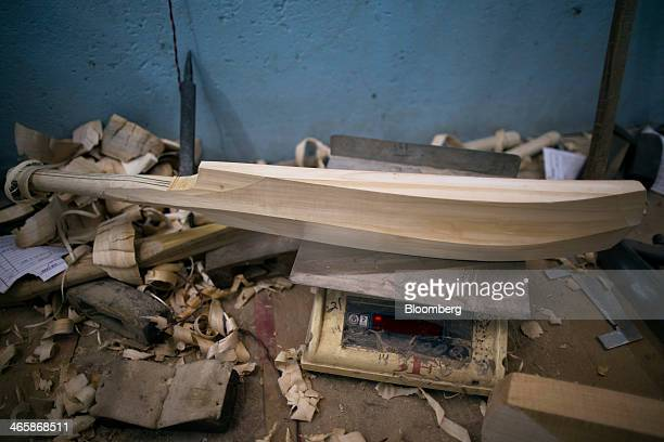 An unfinished cricket bat sits on a set of scales at a Stanford Cricket Industries factory in Meerut Uttar Pradesh India on Wednesday Jan 29 2014 The...
