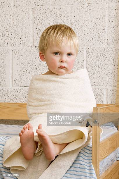 An unhappy baby boy wrapped in a towel sitting on a bed