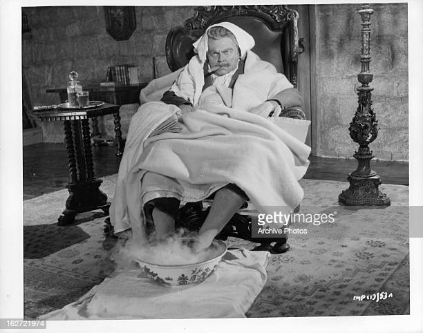 An unhappy Orson Welles sitting covered in blankets in a scene from the film 'Trouble In The Glen', 1954.