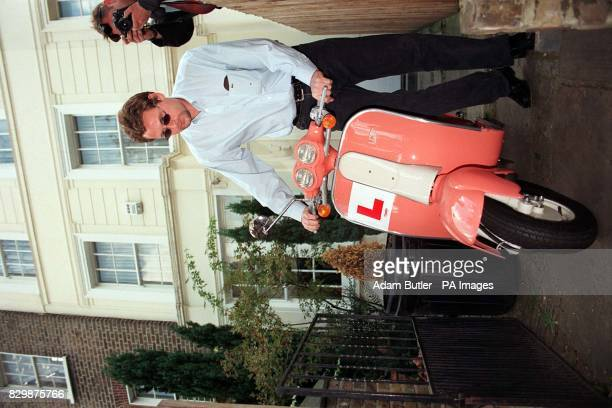 An unidentifed man removes the one of two scooters belonging to Oasis songwriter and guitarist Noel Gallagher from the forecourt of the rock stars'...