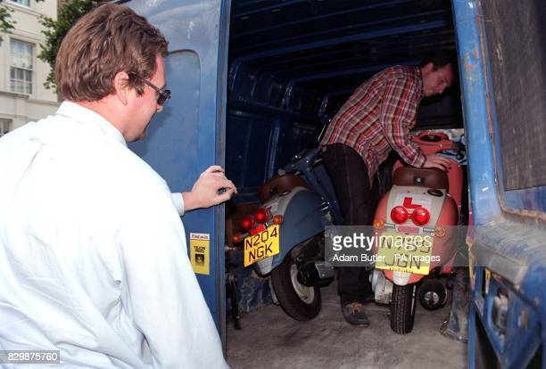 An unidentifed man removes the two scooters belonging to Oasis songwriter and guitarist Noel Gallagher from the forecourt of the rock stars' home...