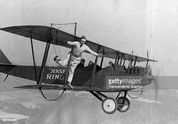 An unidentiffied 'barnstorming' pilot and a wingwalker perform stunts on a Curtiss 'Flying Jenny' biplane in the air above New Jersey 1910s or 1920s