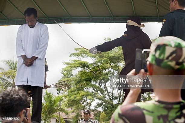 An unidentified Acehnese man is caned in public at the Munawarah Jantho mosque compound in Aceh Besar district in Aceh province after the Friday...