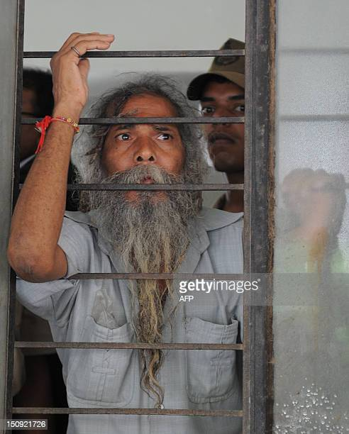 An unidentified acquitted Indian gestures from a Trial Court window in Ahmedabad on August 29, 2012. An Indian court has convicted a former state...