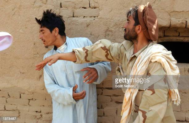 An unidentified Afghan Militia Force soldier slaps a man suspected of harboring foreign prisoners during an interrogation in support of a U.S....
