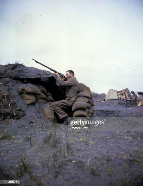An unidentified American sailor from a Navy salvage detachment aims a boltaction rifle into the air from a beachhead bunker Anzio Italy April 15 1944...