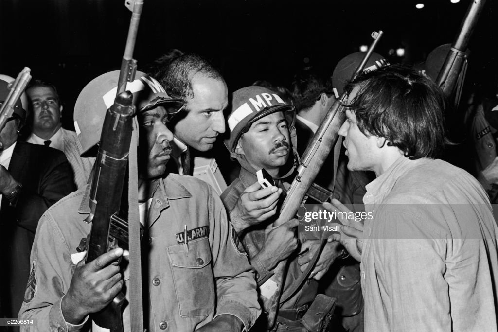 An unidentified anti-Vietnam War protestor confronts two National Guardsmen as a reporter records the exchange outside the 1968 Democratic National Convention, Chicago, Illinois, August 1968.