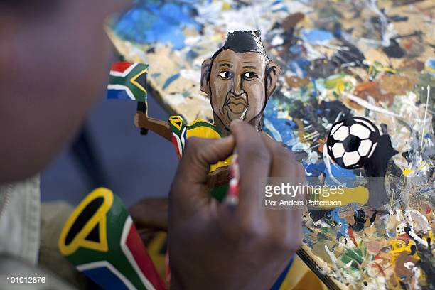 An unidentified artist paints a figure on a Makarapa helmet on April 28 in Alfred Baloyi's studio in Wynberg north of Johannesburg South Africa Mr...