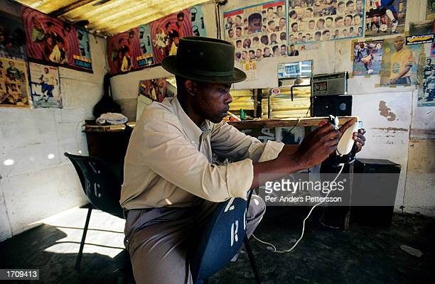 An unidentified barber waits for customers in his shop July 5 2001 in Site C Khayelitsha a township located approximately 21 miles outside Cape Town...
