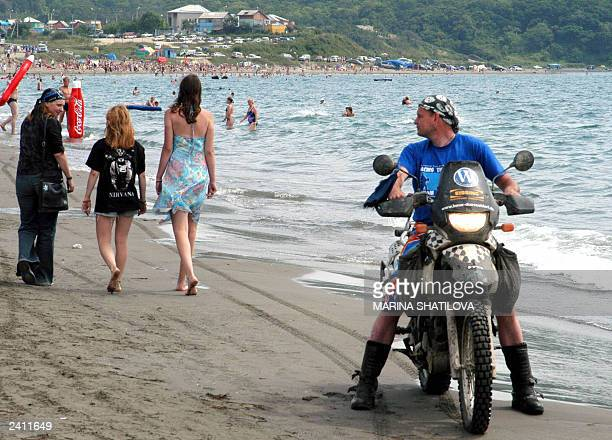 An unidentified biker takes a look at girls passing by Pacific Ocean beach in Vladivostok 17 August 2003 during the first 'Facing the Ocean' festival...